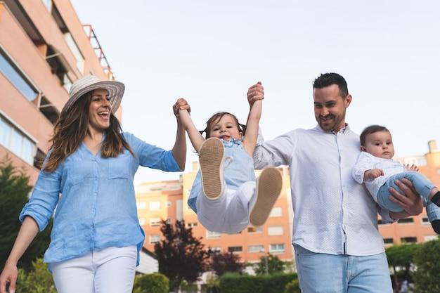 Filha de levantamento dos pares latino-americanos felizes ao ar livre.