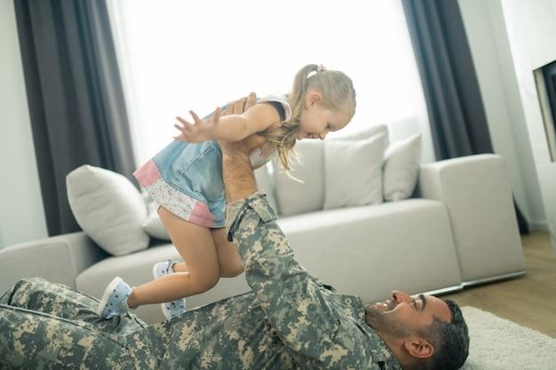 Filha de levantamento. militar sorrindo enquanto está deitado no chão e levanta sua linda filha