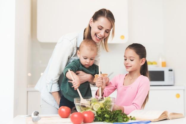 Filha de mãe e bebê preparam uma salada.