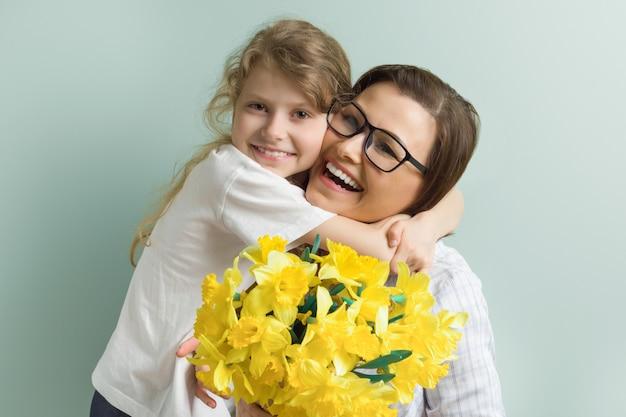 Filha de mãe e filho juntos abraçando com buquê de flores amarelas da primavera