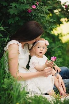 Filha de mãe e filho no jardim primavera. mulher jovem e menina juntas