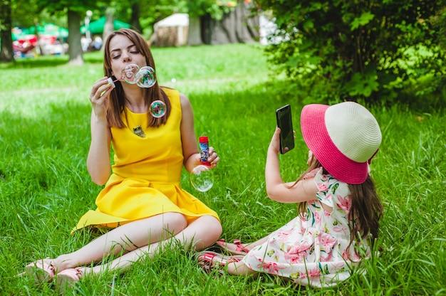 Filha de tirar uma foto de sua mãe ao fazer bolhas