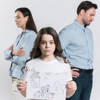 Filha de vista frontal segurando o desenho da família Foto gratuita