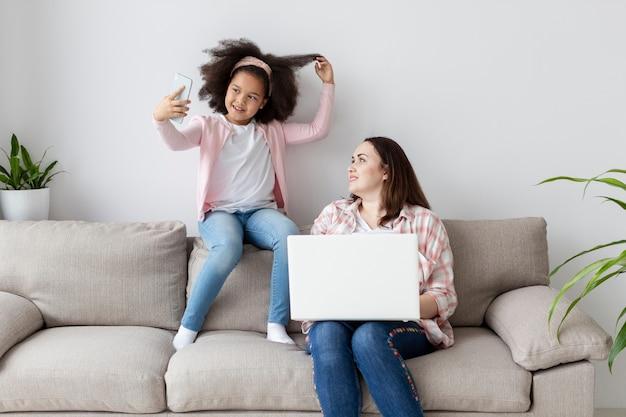 Filha de vista frontal tirando uma foto enquanto a mãe está trabalhando