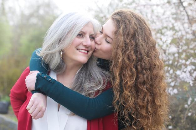 Filha doce beijando e abraçando a mãe