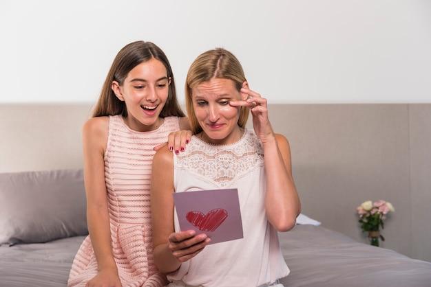 Filha e afetada aos rasgos mãe leitura cartão