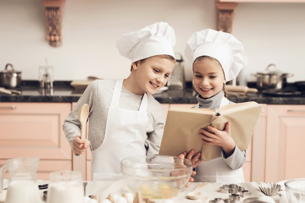Filha e filho feliz cozinhar com livro de receitas.