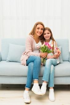 Filha e mãe abraçando-se com flores