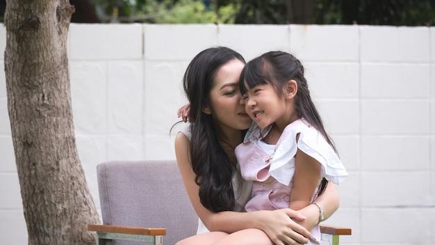 Filha e mãe asiática estão sentadas brincando