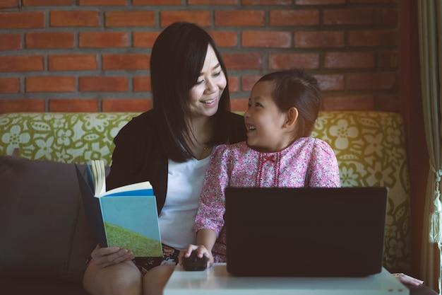 Filha e mãe asiáticas que usam o portátil do computador em casa com sorriso e feliz.