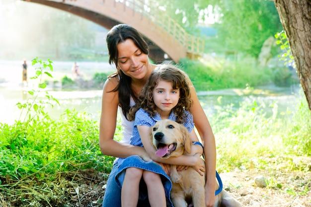 Filha e mãe com golden retriever