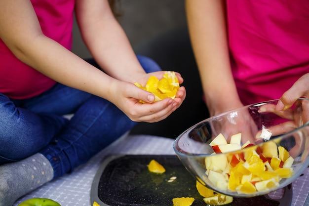 Filha e mãe cortam uma salada de frutas composta de laranja maçã e tangerina