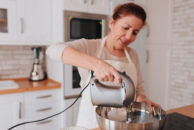 Filha e mãe cozinhando em casa uma sobremesa deliciosa para o dia das mães