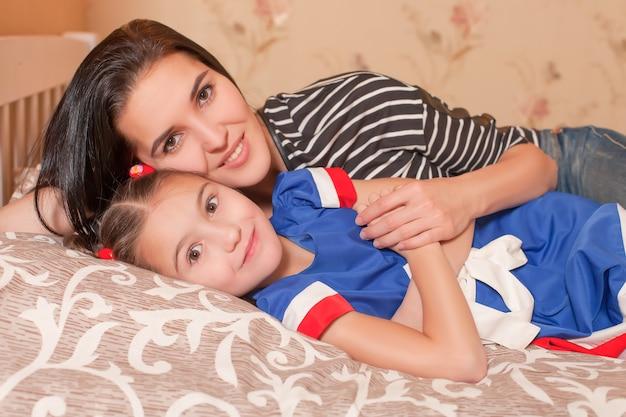 Filha e mãe deita-se na cama.