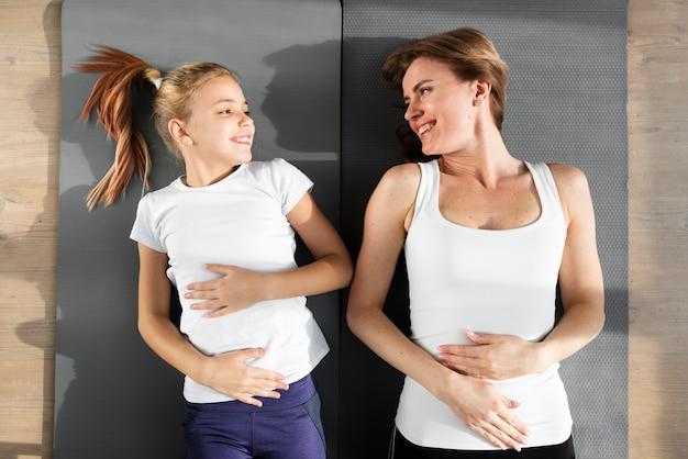 Filha e mãe deitada de costas olhando um para o outro