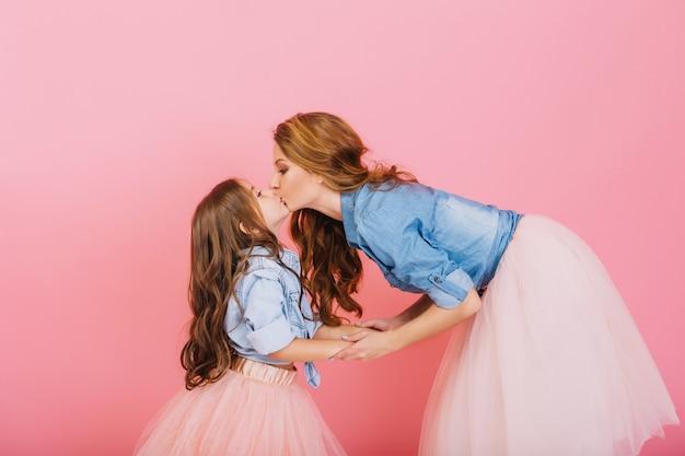 Filha e mãe encaracolada elegante de mãos dadas e se beijam docemente em evento infantil sobre o fundo rosa. menina de cabelos compridos em camisa jeans e saia exuberante beijando sua jovem mãe na festa de aniversário