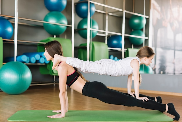 Filha e mãe exercitar juntos no ginásio