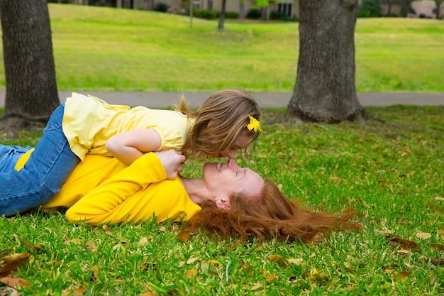 Filha e mãe jogando deitado no gramado do parque