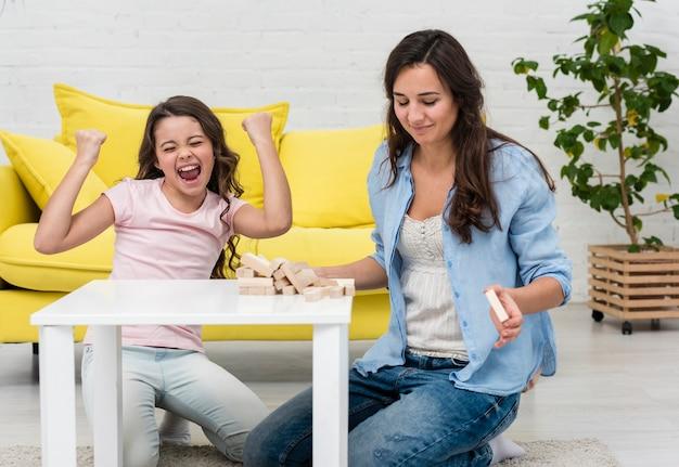Filha e mãe jogando juntos um jogo da torre de madeira