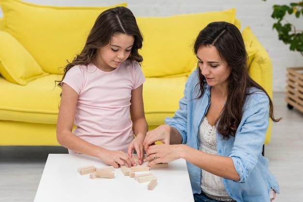 Filha e mãe jogando um jogo da torre de madeira juntos