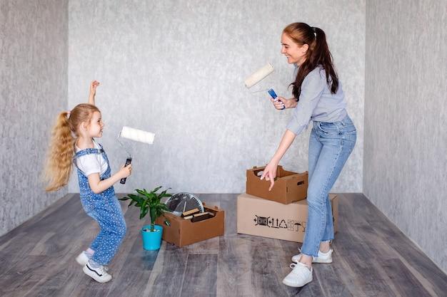 Filha e mãe jovem dançam e brincam com rolos de pintura.