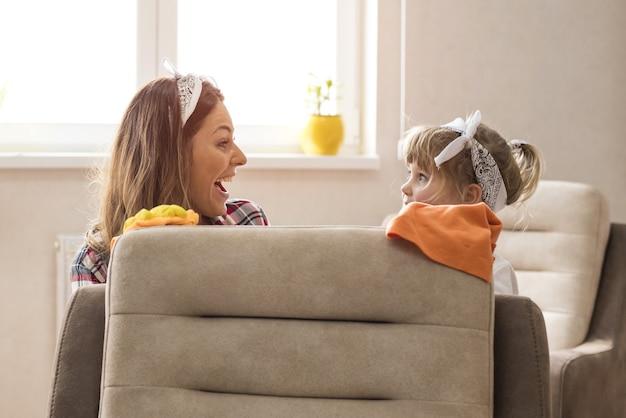 Filha e mãe limpando a casa juntas e se divertindo
