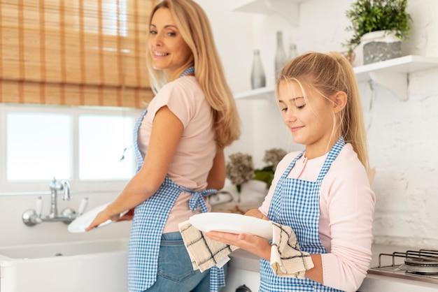 Filha e mãe limpando pratos