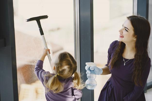 Filha e mãe limpeza janela juntos