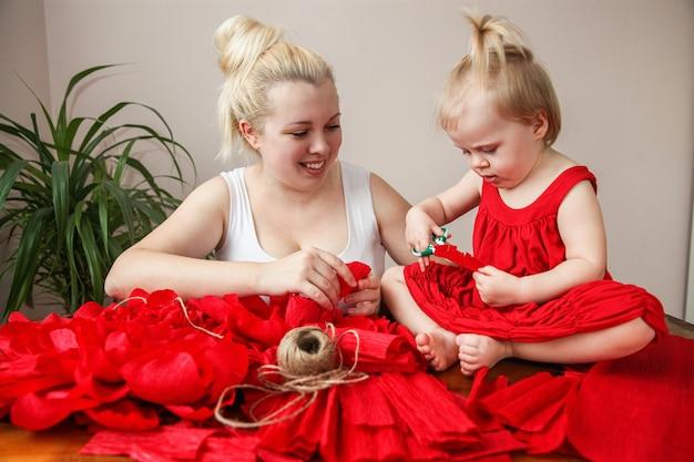 Filha e mãe loira fazem flores de papel vermelho sentadas à mesa em casa. foto de alta qualidade