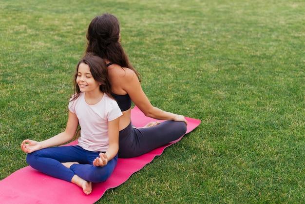 Filha e mãe meditando na grama verde