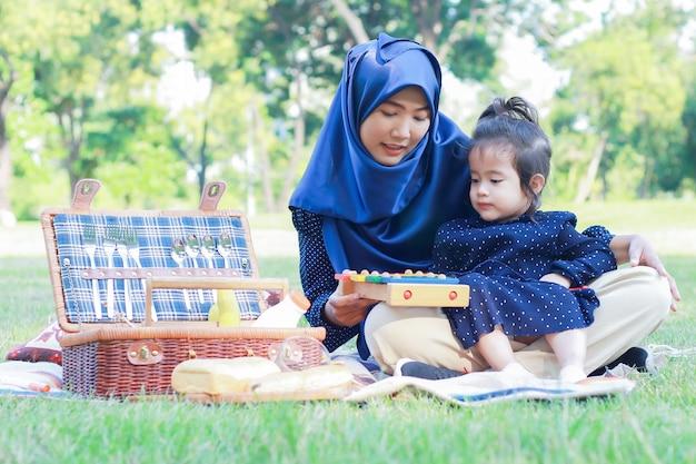 Filha e mãe muçulmana gostam de relaxar no parque.