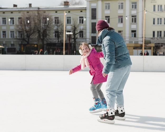 Filha e mãe patinando juntos