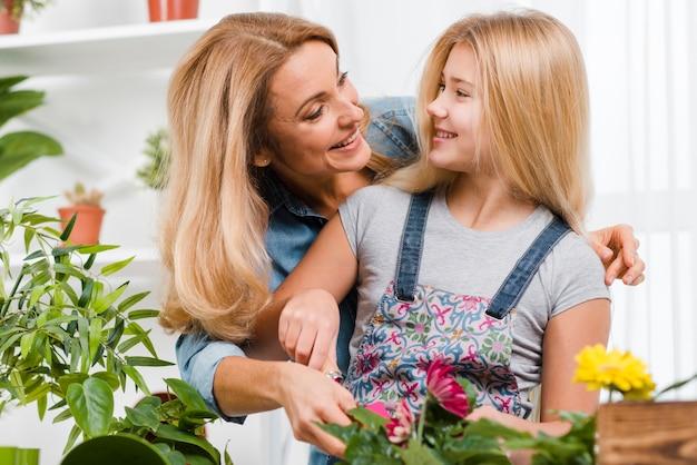 Filha e mãe plantando flores