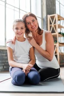 Filha e mãe posando em tapetes de ioga