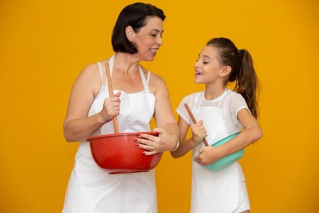 Filha e mãe preparando uma receita