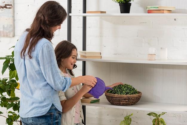 Filha e mãe regando uma planta na cozinha