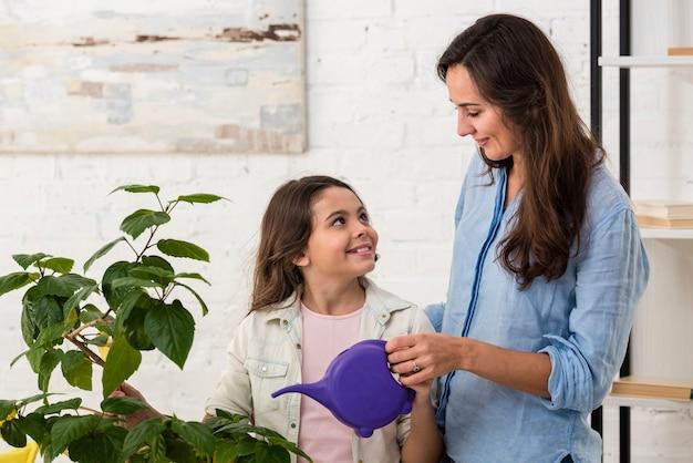 Filha e mãe regando uma planta