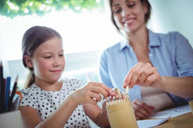 Filha e mãe remover canetas coloridas da caixa