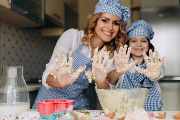 Filha e mãe são mexer a massa e mostrando os braços sujos