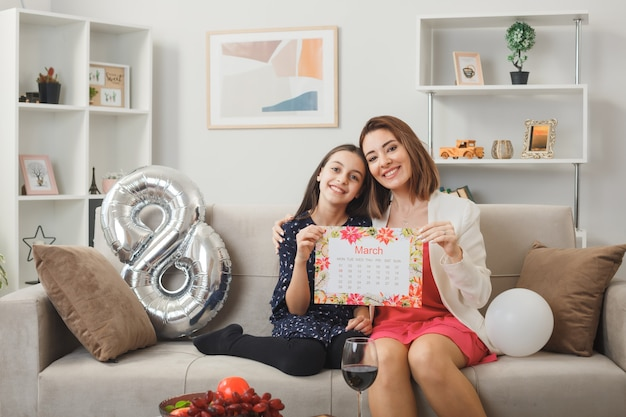 Filha e mãe satisfeitas no feliz dia da mulher segurando a agenda, sentadas no sofá da sala