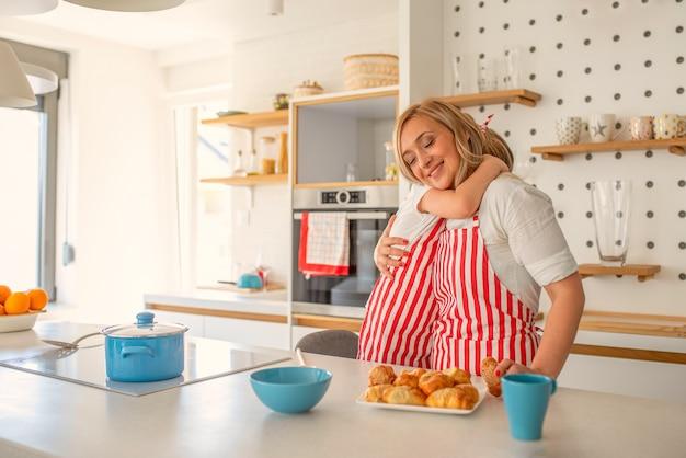 Filha e mãe se abraçando alegremente enquanto cozinham