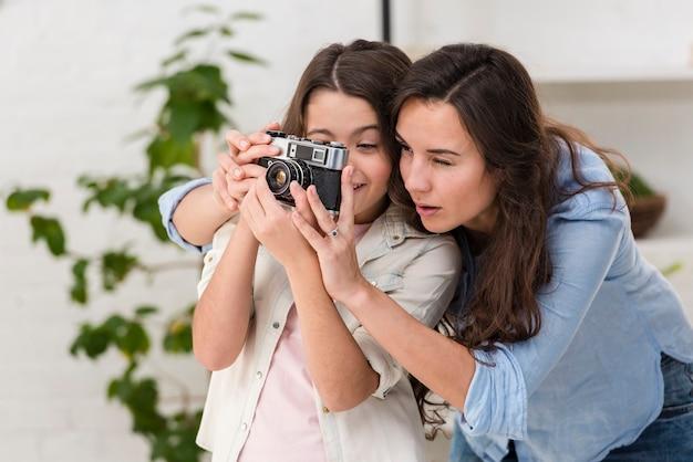 Filha e mãe tirando uma foto com uma câmera juntos