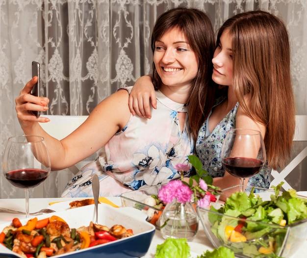 Filha e mãe tomando selfie na mesa de jantar