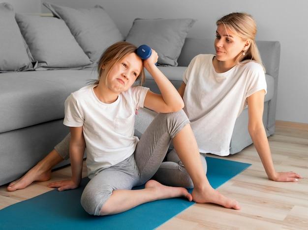 Filha e mãe treinando em casa