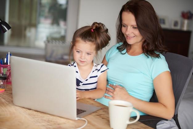 Filha e mãe usam tecnologia por computador