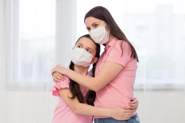 Filha e mãe usando máscaras médicas