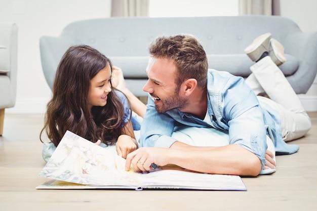 Filha e pai com livro de imagens, deitado no chão