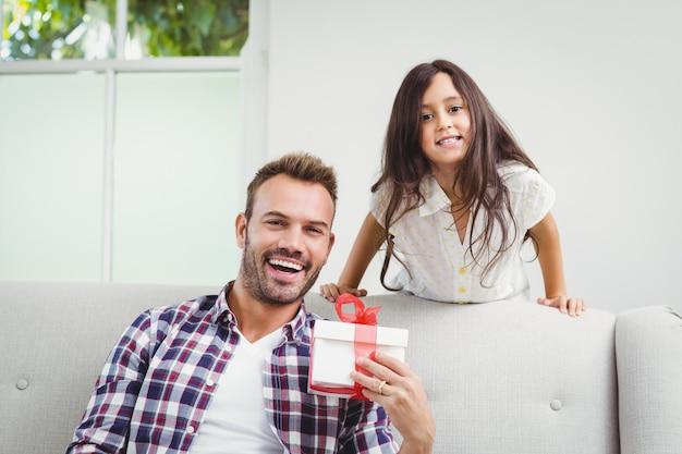 Filha e pai felizes com uma caixa de presente