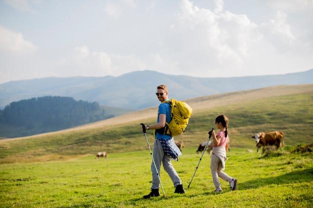 Filha e pai jovem desfrutar de caminhadas em um dia ensolarado