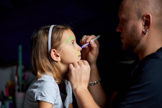 Filha e pai pintam uma cara, se divertindo, lazer juntos em casa no sofá